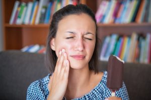 Woman suffering toothache because cold food