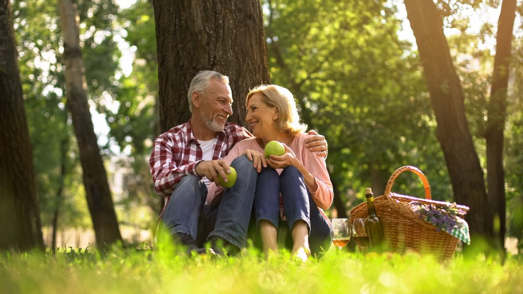 Joyful healthy old couple relaxing on grass, holding apples and hugging, picnic